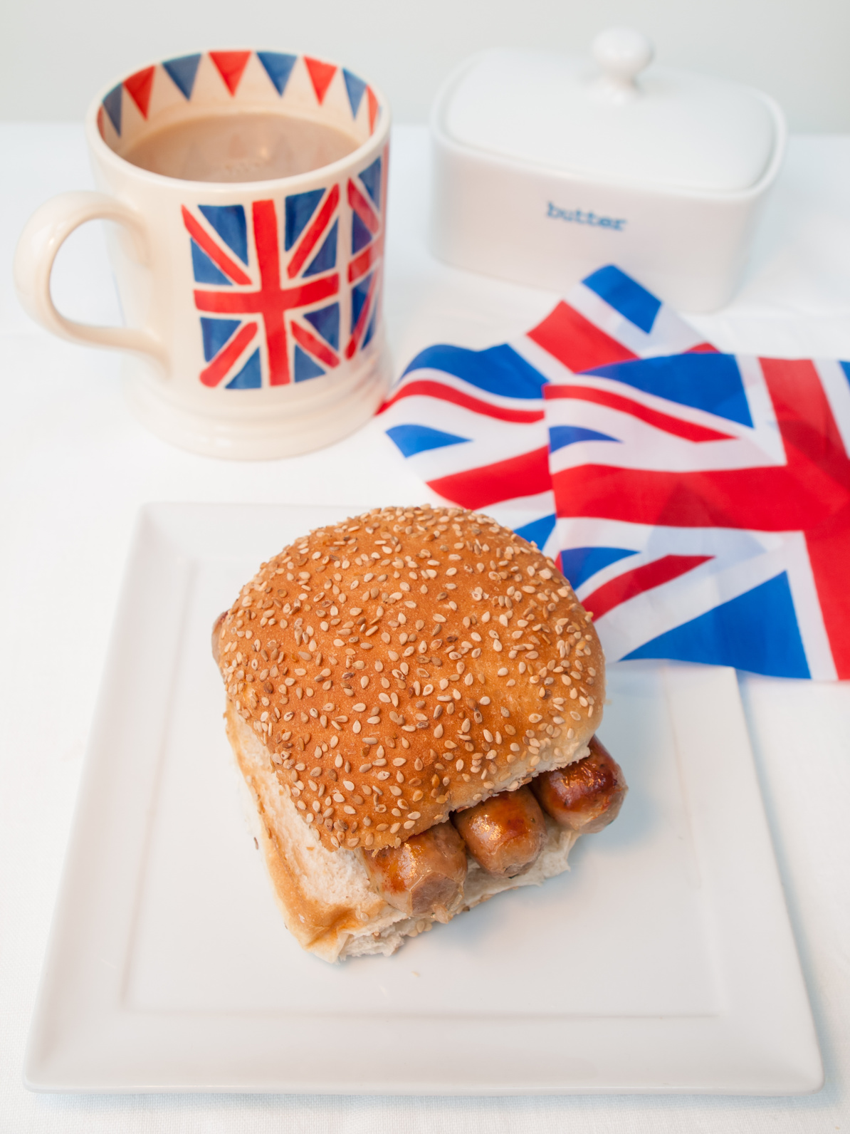 English sausage sandwich with cup of tea in a union jack mug and british union jack flag